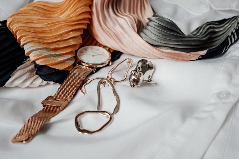 Eine Uhr, Ohrringe und Ringe neben einem Schal - Juwelier Saphir in Augsburg
