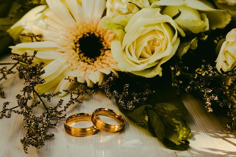 Goldene Trauringe vor dem Brautstrauß - Juwelier Saphir