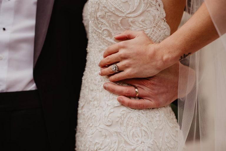 Brautpaar bei der Umarmung mit Fokus auf ihre Trauringe - Juwelier Saphir