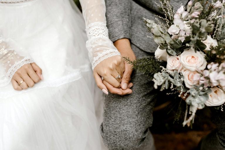 Hände haltendes Brautpaar mit Fokus auf ihre Trauringe - Juwelier Saphir